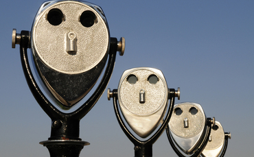 receding-row-of-four-long-range-binoculars-perspective-faces-370x229